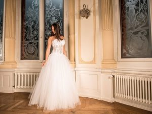 A picture of a bride displaying her wedding dress